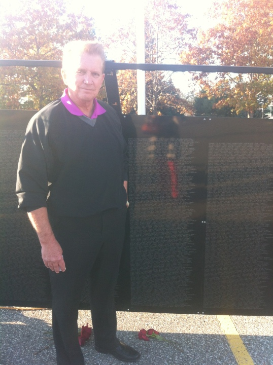 Dad, standing in front of the panel of The Wall that Heals on which his friend's name is etched.