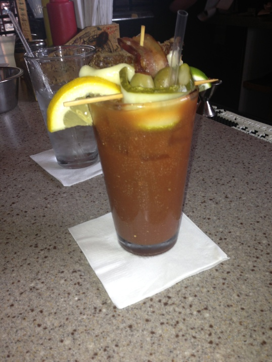 BOMBERS SECRET Bloody  Mary Recipe:garnished  with a lemon, lime, olive,  pickle and our signature  AJ Burger strip with  muenster cheese and bacon. Served with your choice  of domestic shorty.